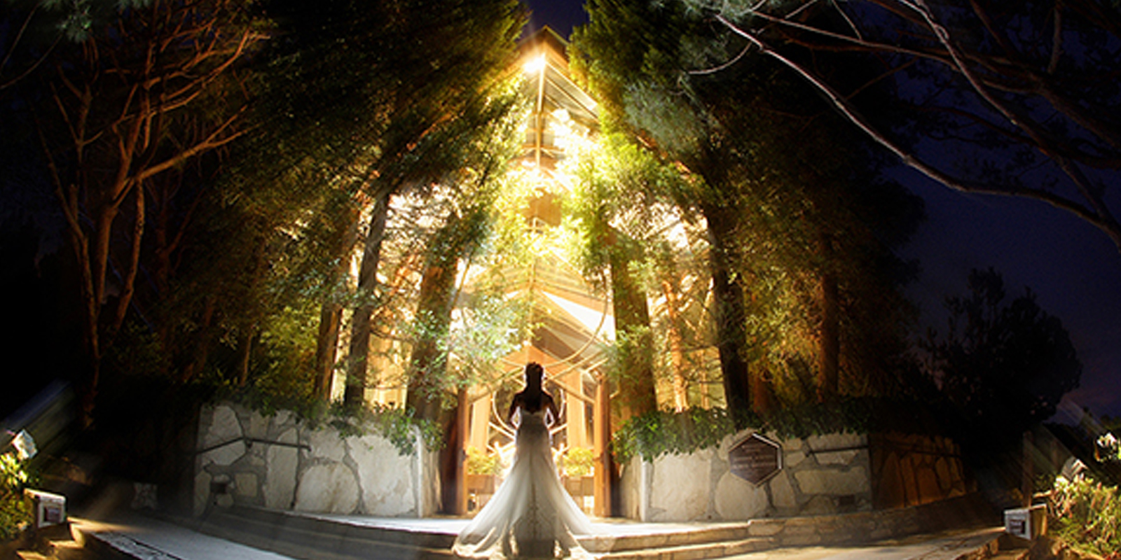 A photo of a bride standing in the doorway of the chapel at night
